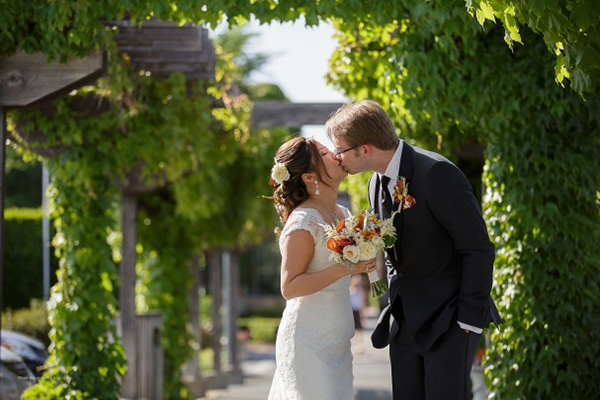 Romantic Kiss Under the Arbor | Rhee Bevere Photography and Caitlin Arnold Weddings | Rustic Elegance for a Vineyard Wedding at The Vintage Estate
